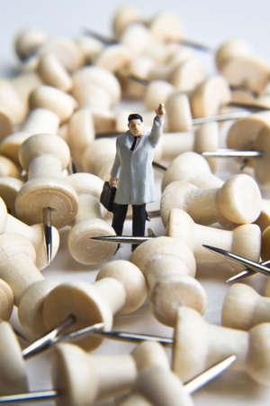 perilous: Businessman figurine placed with tacks
