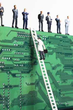 Business figurines and a small ladder placed against a circuit board Stock Photo - 7652914