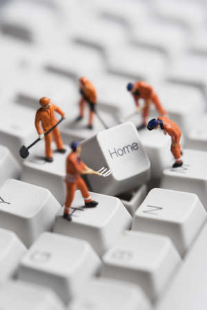 troubleshoot: Worker figurines posed around the Home key on a computer keyboard. Stock Photo