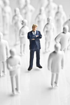 surrounding: Businessman figurine surrounded by white, faceless figurines