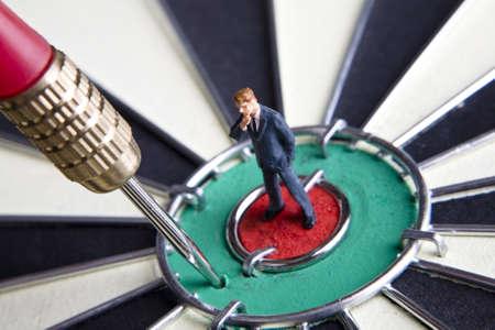 baffled: Businessman figurines placed on a dartboard