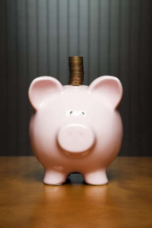 put away: Piggy bank on a table with a stack of pennies on top Stock Photo