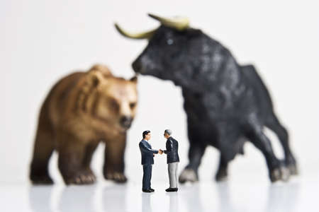 bearish: Business figurines placed with bull and bear figurines.