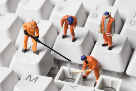 Worker figurines posed to look as though they are working on a computer keyboard. 免版税图像 - 7710111