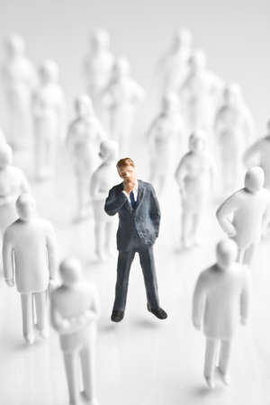 surrounded: Businessman figurine surrounded by white, faceless figurines