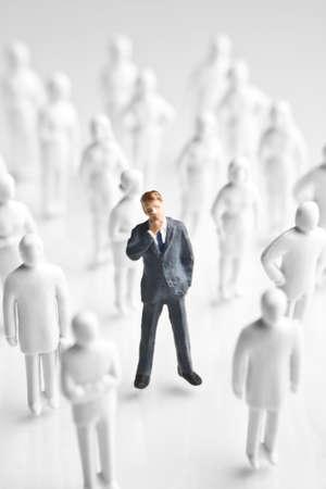 suffocating: Figurina imprenditore circondato da statuette di bianchi, senza volto  Archivio Fotografico