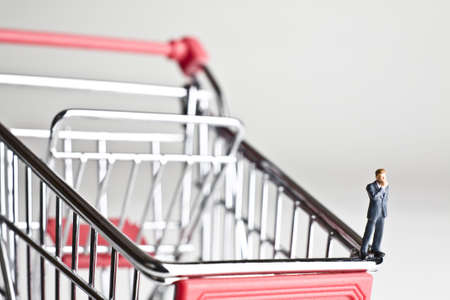 strategizing: Businessman figurines standing on a shopping cart