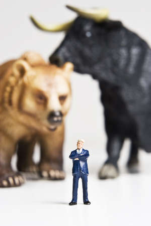 Business figurines placed with bull and bear figurines. Reklamní fotografie - 7792609