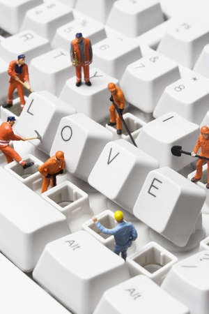 troubleshoot: worker figurines posed around the word love spelled out with compute keys, on a keyboard.