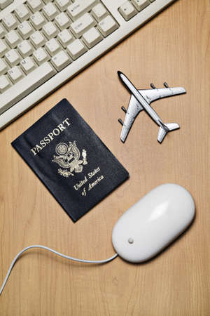 White computer mouse, toy airplane and passport on a wood tabletop