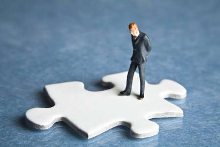 strategizing: Businessmen figurines and puzzle pieces