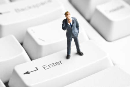 strategizing: Businessman figurine on computer keyboard