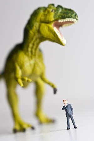 chomp: Dinosaur figurine placed behind a businessman figurine