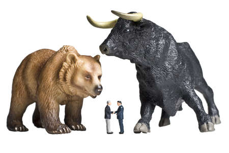 Business figurines shaking hands placed in front of bull and bear figurines.