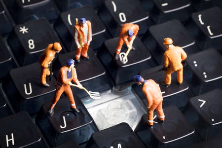 Worker figurines posed to look as though they are working on a computer keyboard. Stock Photo - 7792758