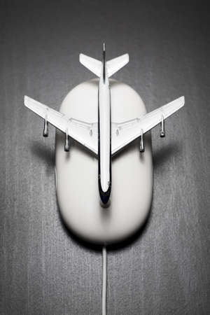 Toy airplane on computer mouse