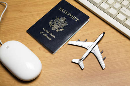 reservation: White computer mouse, toy airplane and passport on a wood tabletop