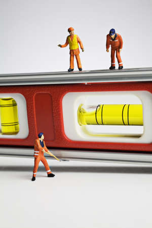 figurines: Worker figurines and a level Stock Photo