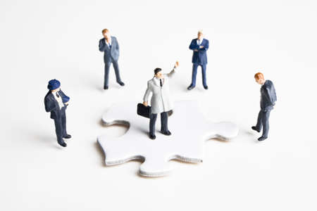 figurines: Businessmen figurines and puzzle pieces