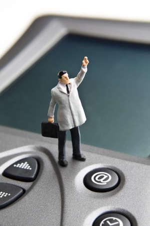 strategizing: Businessman figurine on a PDA