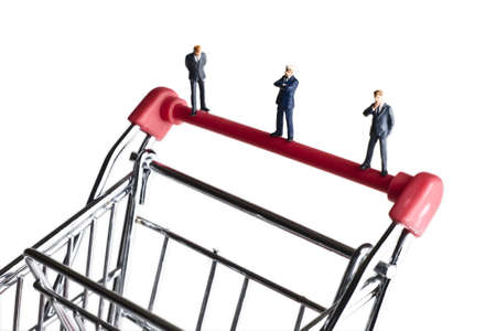 strategizing: Businessman figurines on a shopping cart
