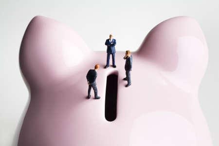 strategizing: Businessman figurines on a piggy bank Stock Photo