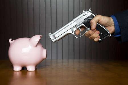 stickup: Man pointing a gun at a piggy bank