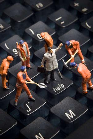 Werknemer beeldjes gesteld aan het kijken alsof ze op een computer toetsen bord werken. Stockfoto