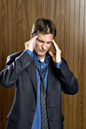 Businessman experiencing a headache rubbing his temples  Banco de Imagens