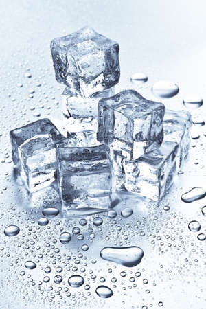 Melting ice cubes on a metal tabletop Imagens