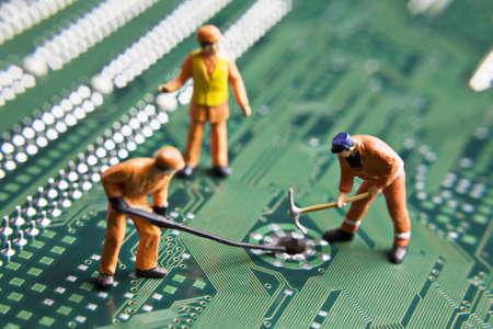 repairing: Figurillas de trabajador colocadas sobre una placa de circuito de equipo  Foto de archivo