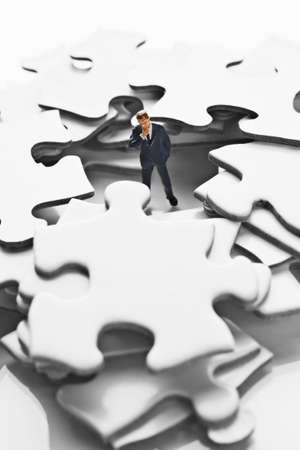 strategizing: Business figurine on puzzle pieces