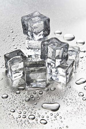 Melting ice cubes on a metal tabletop Stok Fotoğraf