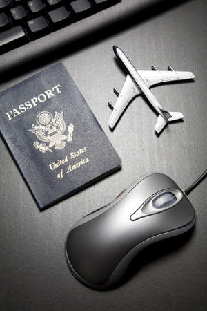 Metallic computer muis, speel goed vlieg tuig en paspoort op een zwarte houten tafel blad Stockfoto