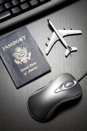 agencia de viajes: Rat�n de ordenador met�lico, el avi�n de juguete y el pasaporte en una mesa de madera negra
