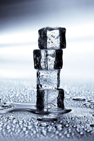 Melting ice cubes on a metal tabletop photo