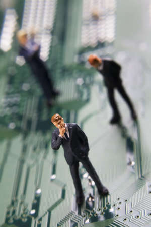 Business figurines placed on a computer circuit board