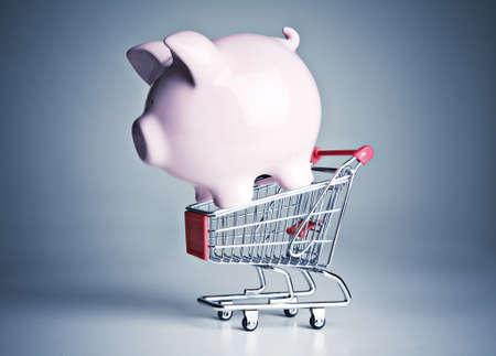 Piggy bank on a miniature shopping cart photo