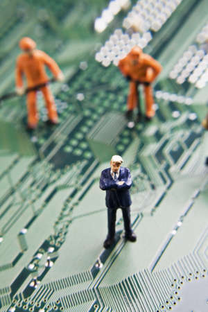 Business and worker figurines placed on a computer circuit board Stock Photo