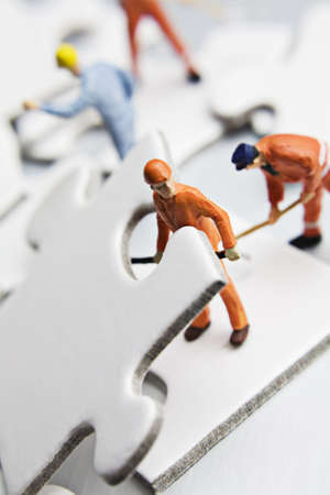 strategizing: worker figurine with white jigsaw puzzle pieces