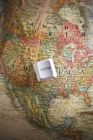 Home computer key on an earth globe Stock Photo