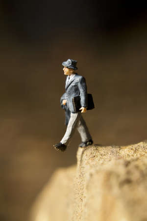 Businessman figurine posed to look like it is walking off a cliff Banco de Imagens - 7989639