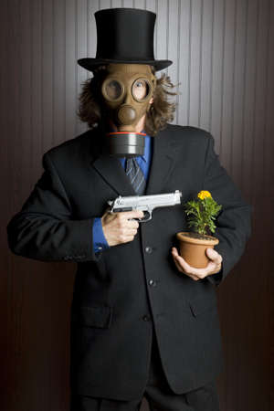 Businessman wearing a gasmask holding a gun to a flower  photo