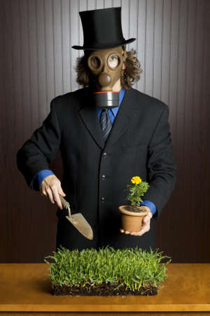 Businessman wearing a gasmask holding a potting shovel standing over a patch of grass