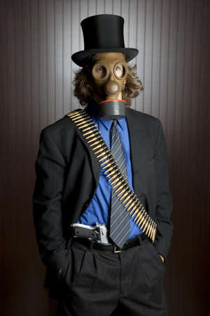 gasmask: Businessman wearing a gasmask and a bullet belt with a gun tucked into his pants