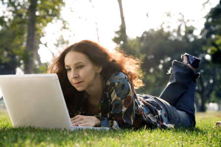45 55 years: middle age woman, wearing a hearing aid, working on her laptop in a park. Stock Photo
