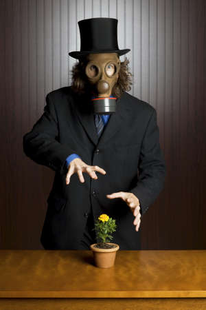 Businessman wearing a gasmask waving his hands over a flower on a table  photo