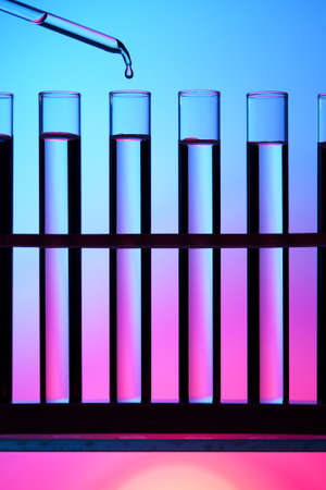 fda: Test tubes and dropper against a colorful background