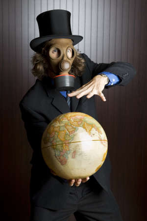 peculiar: Businessman wearing a gasmask holding an earth globe