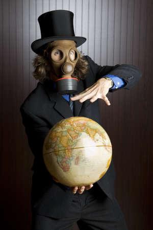 gasmask: Indossa una maschera antigas uomo d'affari in possesso di un globo terrestre